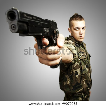 portrait of caucasian soldier with jungle camouflage pointing with pistol over grey background - stock photo