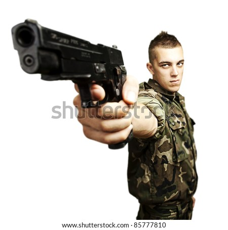 portrait of caucasian soldier with jungle camouflage pointing with pistol over white background - stock photo