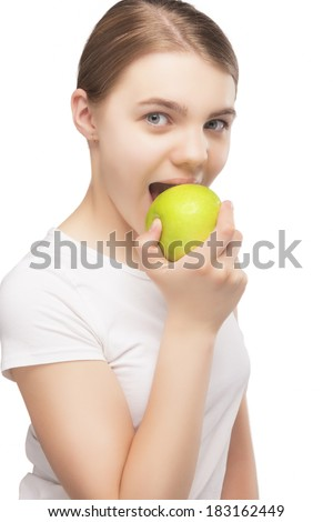 Portrait of Caucasian Teenager Girl Eating Delicious Green Apple.Isolated Over Pure White  Background. Vertical Image - stock photo
