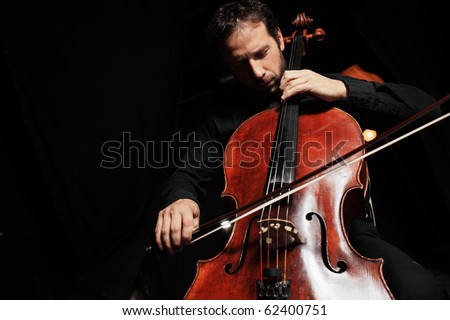 Portrait of cellist playing classical music on cello on black background. Copyspace. - stock photo