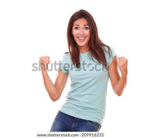 Portrait of charming adult woman on blue t-shirt and blue jeans celebrating her victory while smiling at you with funny face and standing on isolated studio