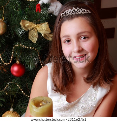 Portrait of charming beautiful little girl with candle on christmas o Holiday theme/Portrait of young princess girl wearing teara and holding christmas candle