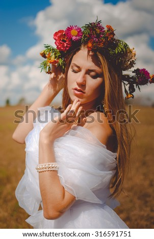 Portrait of charming beautiful woman in flower wreath and white chiffon dress. Romantic bride on summer countryside background. - stock photo