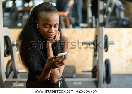 Portrait of charming black young woman with luxury long hair texting on her smartphone in the gym - stock photo