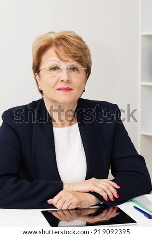 Portrait of charming businesswoman sitting at the desk in the office.  - stock photo