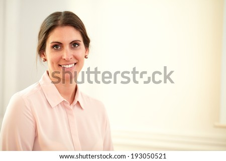 Portrait of charming executive female on pink blouse smiling at you while standing on closeup background - copyspace