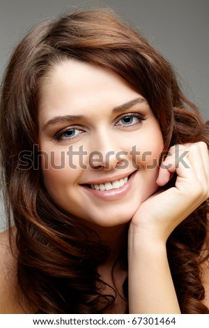 Portrait of charming girl touching her face and looking at camera - stock photo