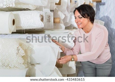 Portrait of charming positive smiling mature woman with cloth rolls  in textile store - stock photo