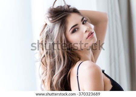 Portrait of charming sensual young female with long hair standing in lingerie - stock photo