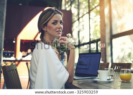 Portrait of charming smiling businesswomen posing while resting after work on her portable laptop computer during coffee break, young pretty female using net-book while sitting in modern cafe interior - stock photo