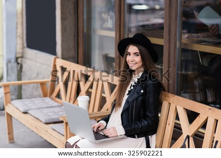 Portrait of charming smiling woman using net-book for remote job while sitting on a bench outdoors, happy attractive female freelancer working on portable laptop computer during her recreation time  - stock photo