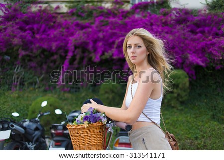 Portrait of charming stylish caucasian female enjoy a rest after an active riding through the city on her classic bicycle, woman standing against beautiful flowers and greenery fence with copy space - stock photo