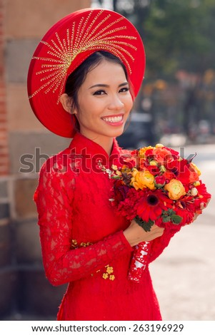 Portrait of charming Vietnamese bride with bouquet of flowers - stock photo