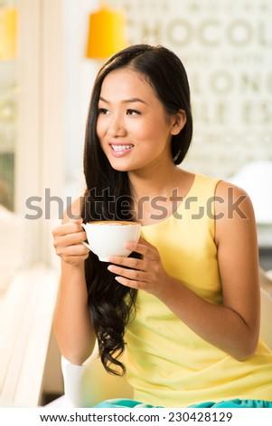 Portrait of charming Vietnamese woman drinking tea - stock photo