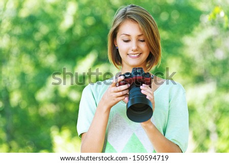 portrait of charming young beautiful short-haired woman in profile, photographs, against background of summer green nature - stock photo
