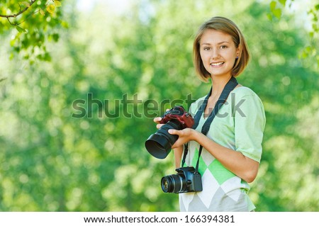 portrait of charming young beautiful short-haired woman in profile, photographs, against background of summer green nature