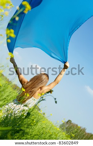 Portrait of charming young girl raising her hands with blue chiffon in the field - stock photo