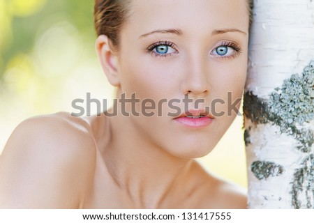 Portrait of charming young woman close up with bare shoulders near birch, against background of summer green park. - stock photo