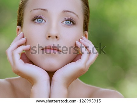 Portrait of charming young woman close up with bared shoulders, against background of summer green park. - stock photo