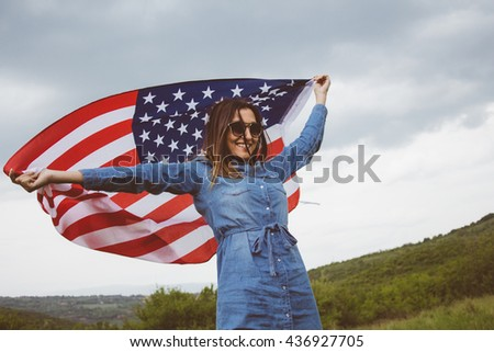 Portrait of charming young woman with an american flag. She is wearing stylish denim dress and fashionable sunglasses, as well as her lovely smile.Natural backgrounds. Summer. Holidays. - stock photo