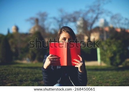 Portrait of charming young woman with red book held up close to her face, cute female covering half face with a book while sitting in the park at sunny afternoon, filtered image - stock photo