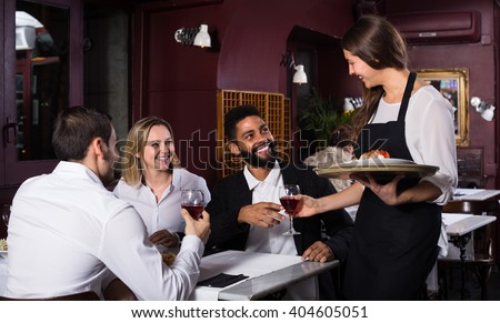 Portrait of chatting friends in restaurant and cheerful waitress - stock photo