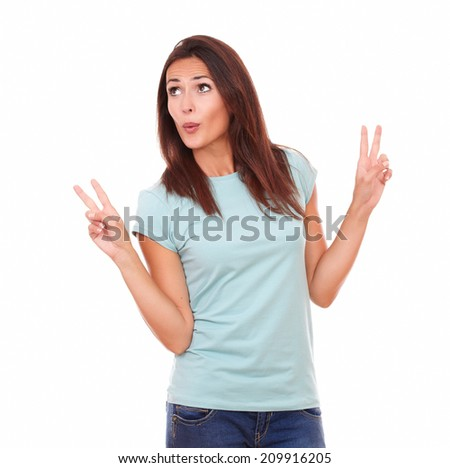 Portrait of cheerful adult woman on blue jeans celebrating her victory while looking to right up and standing on isolated white background - copyspace - stock photo