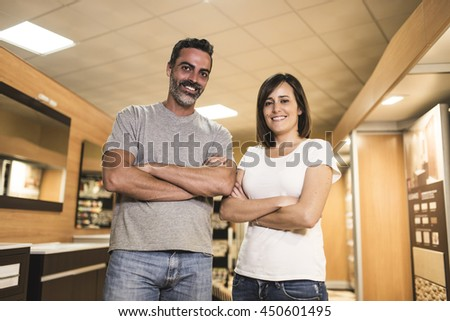 Portrait of cheerful adults with crossed arms smiling at camera in bathroom store