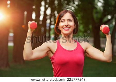 Portrait of cheerful aged woman in fitness wear exercising with red dumbbells in park. - stock photo