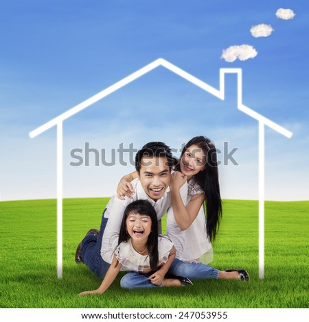 Portrait of cheerful asian family playing at field under a dream house symbol