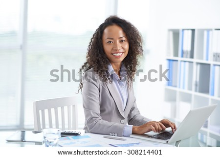 Portrait of cheerful Asian office manager working on laptop