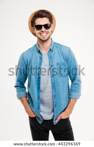 Portrait of cheerful attractive young man in hat and sunglasses over white background - stock photo