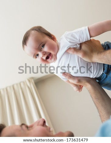 Portrait of cheerful baby boy being carried by father at home - stock photo