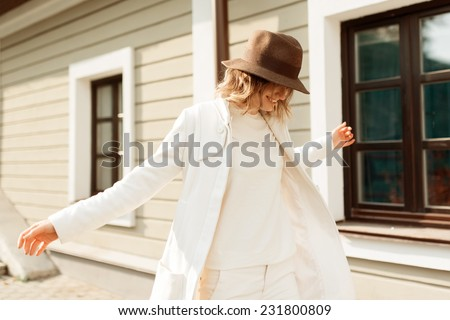 Portrait of cheerful beautiful fashionable woman in a hat and coat - stock photo