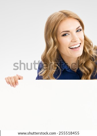 Portrait of cheerful beautiful woman showing blank signboard with copyspace area for text or slogan, over grey