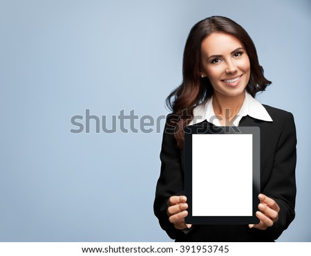 Portrait of cheerful beautiful young brunette businesswoman showing blank no-name tablet pc monitor, over grey background, with copyspace area for slogan or text message