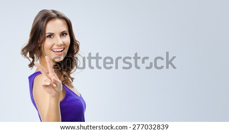 Portrait of cheerful beautiful young woman in smart casual violet clothing, showing two fingers or victory gesture, against grey background, with blank copyspace area for slogan or text - stock photo