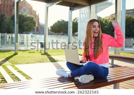 Portrait of cheerful blonde hair female student waving to someone sitting on the campus bench at beautiful sunny day, happy female teenager greeting hello while sitting with open laptop outdoors - stock photo