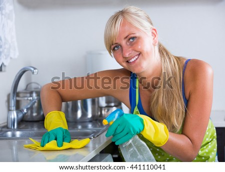 Portrait of cheerful blondie dusting in residential kitchen - stock photo