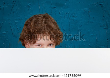 Portrait of cheerful boy pointing on white banner - stock photo