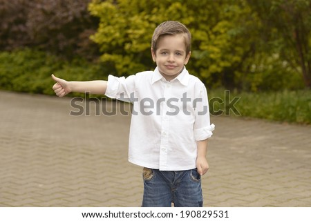 Portrait of cheerful boy showing thumbs up gesture - stock photo