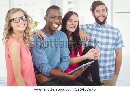 Portrait of cheerful business people with man holding digital tablet in creative office - stock photo