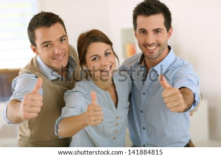 Portrait of cheerful business team showing thumbs up