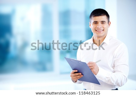 Portrait of cheerful businessman making notes and looking at camera - stock photo
