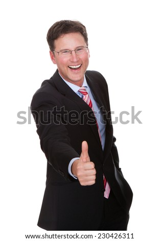 Portrait of cheerful businessman showing thumbsup against white background - stock photo