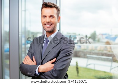 Portrait of cheerful businessman standing in office - stock photo