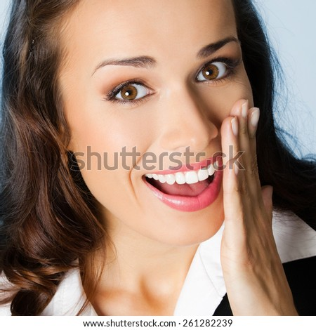Portrait of cheerful businesswoman covering with hand her mouth, against blue background - stock photo