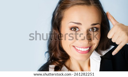 Portrait of cheerful businesswoman showing call me gesture, against blue background - stock photo