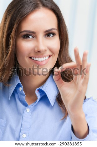 Portrait of cheerful businesswoman showing okay hand sign gesture, at office - stock photo