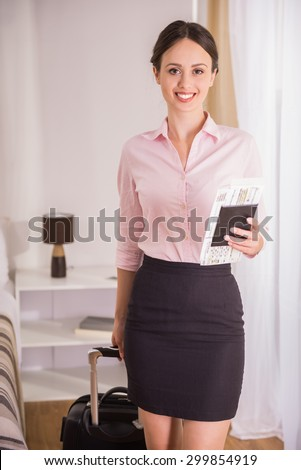 Portrait of cheerful businesswoman with her documents and suitcase at the hotel room. - stock photo
